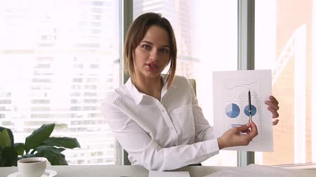 falante : Businesswoman holding paper financial report talk at webcam make video call in office, business coach looking at camera speak show statistics explain marketing strategy for client, online training