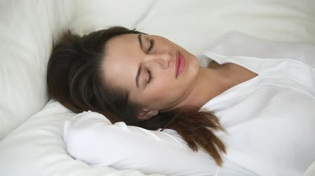 белье : Calm young woman with beautiful face sleeping well in cozy comfortable bed on soft pillow, serene attractive lady resting lying asleep enjoying peaceful healthy good sleep on white sheet cotton linen