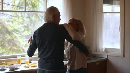 中世の : Happy mature senior couple dancing laughing in the kitchen, beautiful romantic middle aged older grandparents relaxing having fun together at home celebrating anniversary enjoy care love tenderness 動画素材
