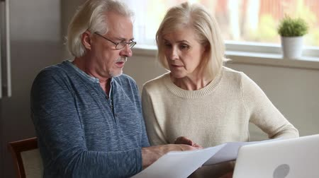 factuur : Serious senior mature couple talking disputing holding paper bills checking finances expenses, older middle aged family reading bank loan payments documents at home worried about debt money problems