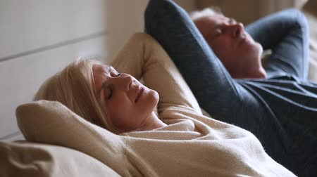 plezant : Calm senior middle aged couple relaxing leaning on comfortable soft couch having healthy nap together, happy old mature man and woman enjoy satisfaction chill feeling no stress free resting at home