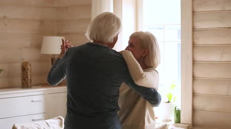 plezant : Happy senior romantic couple dancing in modern country house living room, loving old middle aged family grandparents husband and wife enjoy tender moment celebrating anniversary relaxing together