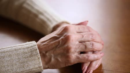 luto : Old lonely mature female wrinkled skin hands folded on table close up view, middle aged senior elderly woman grandmother having arthritis rheumatism, health care, aging process and loneliness concept