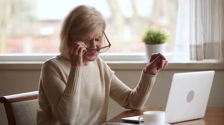 sindrome : Senior woman using laptop feeling discomfort from dry irritated fatigued eyes taking off glasses, older mature businesswoman tired of computer worker suffering from blurry vision eyestrain problem