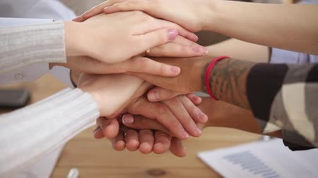 hűség : Diverse people stacking hands together in pile, multi ethnic students sales team engaged in corporate teambuilding connected in teamwork help support coaching training unity concept, close up view Stock mozgókép