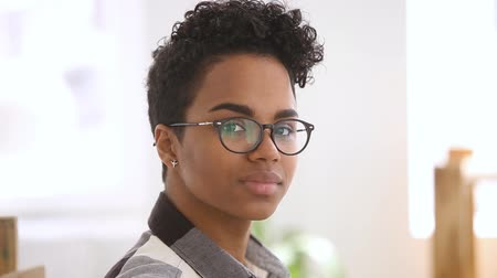 internar : Happy confident african american girl student with stylish haircut wearing optical glasses looking at camera, smiling millennial black mixed race woman professional posing alone for video portrait Stock Footage