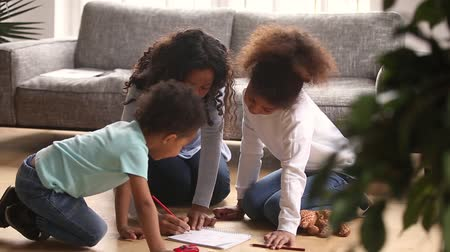 babysitter : Caring african mother baby sitter drawing with colored pencils teaching two little kids sitting on warm floor at home, loving black mom helping children play together, creative family hobby activity Stock Footage