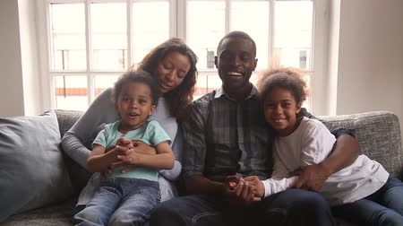 youtube : Happy african american family with children son daughter wave hands looking at camera make online video call together at home, smiling black mom dad and kids talking at webcam recording vlog portrait