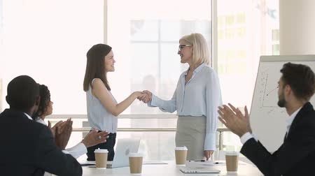 internar : Happy female mature boss manager handshaking praising young employee congratulating with promotion hiring successful intern, rewarding appreciating while diverse team applauding, employee recognition