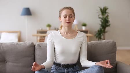 breathing fresh air : Calm serene young woman sitting on couch in lotus position doing yoga exercise at home, happy mindful healthy girl relaxing meditating on sofa breathing feeling balance harmony no stress free concept