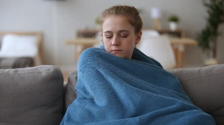 em casa : Sick ill upset young woman feeling cold fever freezing no central heating problem at home covering with warm plaid blanket shivering sitting on couch got flu influenza virus grippe symptoms concept.