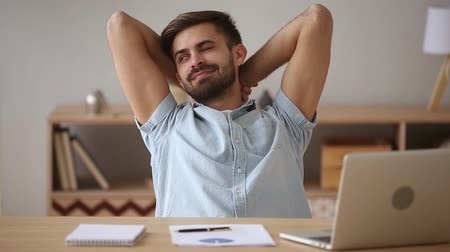 compleição : Relaxed happy young man taking break chilling satisfied with finished laptop work well done resting sit at desk stretching hands behind head enjoy peaceful mood lounge no stress free relief concept.