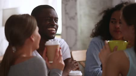 kawa filiżanka : Happy african guy joking having fun laughing talking to multiracial young friends students at group meeting in cafe drinking coffee tea together sitting at cafe table, multi-ethnic friendship leisure Wideo