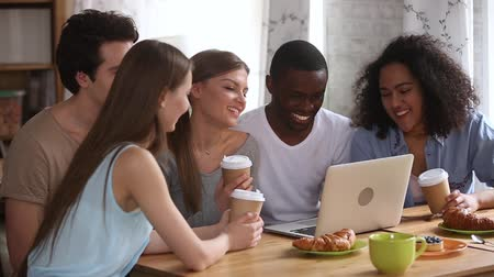 集まる : Happy young diverse friends having fun watching comedy movie, online tv show or funny social media video on laptop, multiracial millennial people students group laughing use computer together in cafe 動画素材