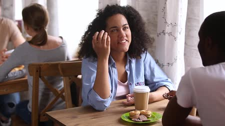 plezant : Happy african girl enjoying first date with black guy friend talking laughing sitting at cafe table, smiling mixed race young woman flirting meeting boyfriend having fun drinking coffee together