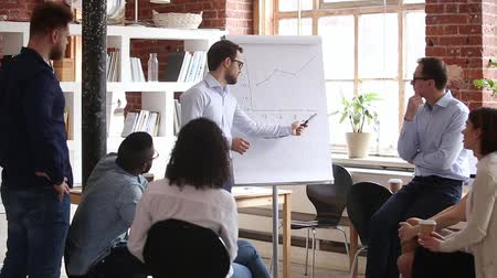 тренировка : Confident speaker coach gives corporate presentation on whiteboard teaching diverse sales team at group meeting, male business trainer presenter speaking at training explaining report graph in office