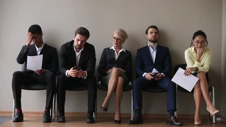vaga : Different ages and ethnicity candidates for vacancy sits on chairs in queue corridor feels nervous bored waits job interview turn, business people holds phones cv papers, recruitment hiring hr concept