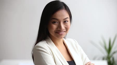 stagiair : Head shot asian ethnicity millennial businesswoman or company employee standing in office room crossed arms looks at camera laughing feels confident. Team leader, business coach portrait or hr concept