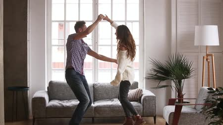 amado : Active couple celebrate moving day at new first home flat, husband holds hand beloved wife spinning dancing together in living room, man lifting cuddle woman, happy family enjoy relocation day concept Stock Footage