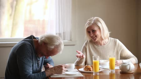plezant : Aged family eating healthy breakfast drink morning coffee sitting at table in kitchen at home blond wife telling funny story husband hoary man laughing, spouses enjoy time together, humor mood concept