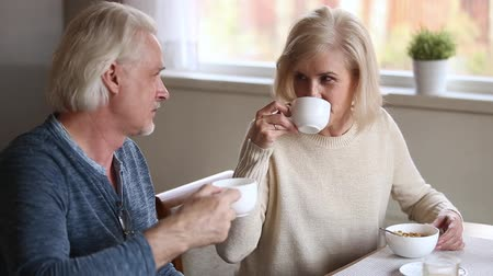 plezant : Elderly attractive spouses having pleasant conversation holding cups with morning coffee sitting at table in kitchen at home, mature family discussing plans for weekend chatting laughing feels happy