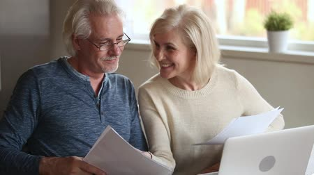 facil : Elderly couple holds bills makes online payment use pc, check bank account balance feels satisfied, wife explains help to husband do transaction, easy secure money remittance modern tech usage concept