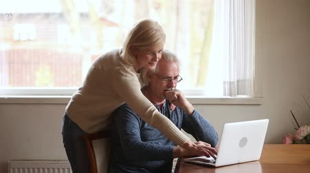 facil : Elderly couple use laptop wife helps husband with new apps, online banking electronic services, buy ticket via internet planning travel, choose eyewear browse website, easy usage wireless tech concept