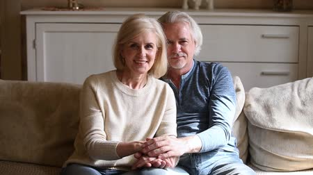 amado : Grey haired elderly couple in love sitting on couch holds hands looking at camera feels happy, mature loving spouses indoors, healthy retirees resting at modern home enjoy time with each other concept Stock Footage