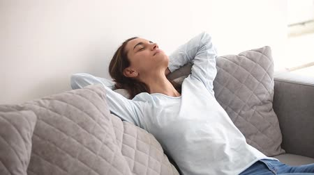 devanear : Young woman in casual wear closed eyes putting hands behind head breath fresh air resting on comfortable couch in living room at home leaning on sofa feels serenity, stress relief and daydream concept Stock Footage