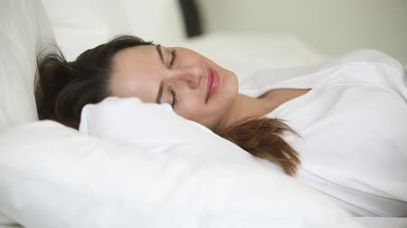 bastante : Close up of serene woman closed eyes smiles sleeps on bed on her back lying on white fresh bedding comfortable pillow orthopaedic mattress feels healthy resting at home or hotel, enjoy day nap concept