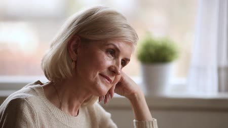 remembering : Close up face elderly healthy blond woman sitting resting at home head rests on the hand smiling thinking remembering past happy memories, lost in positive thoughts, satisfied with her retirement life Stock Footage