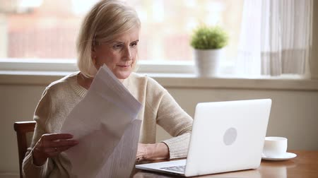 makbuz : Elderly stressed woman sitting at table in kitchen at home holds domestic bills use laptop makes online payments feels concerned forgot to pay or debt formed, check finances financial problems concept