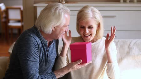 make friends : Aged husband prepare holds pink gift box while wife closed eyes with hands await feels happy, positive mature family sitting at home on sofa woman feels gratitude kiss beloved man thanks for surprise