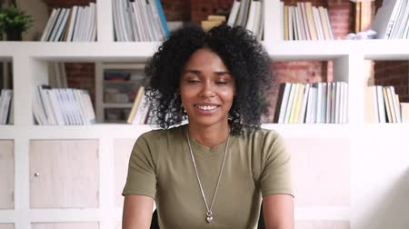 forgatás : Smiling african american young woman student online teacher looking at camera webcam making video call to distant friend or job interview, happy mixed race blogger talking at webcamera recording vlog