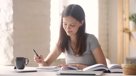 essay : Teen girl high school college university student learning making notes writing essay in notebook doing academic research preparing for exam coursework work with books sitting at desk studying at home.