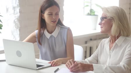 persuasion : Young saleswoman insurer advisor consulting old female client looking at laptop showing business presentation, broker manager having conversation convincing customer to take loan or buy bank services