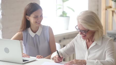 negotiations : Satisfied old woman client and young manager handshake signing contract agreement in office, happy senior customer with smiling insurance broker saleswoman make business services loan deal shake hand Stock Footage