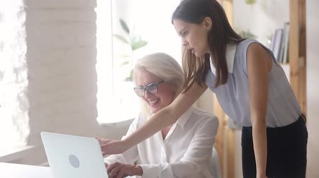 collaborating : Young female teacher mentor manager coach teaching helping old worker explain instructing pointing at laptop computer, different age generations talk work together learn new skill in office workplace Stock Footage