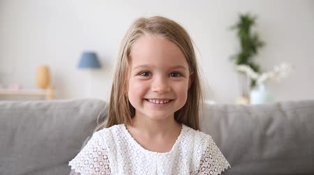 telefonia : Funny little girl smiling looking at camera at home, cute kid talking to webcam making online video call or recording vlog having fun, preschool child with pretty face waving hand sitting on sofa