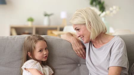 dizer : Cute little granddaughter talking to grandma having fun telling funny story sitting on sofa, pretty kid girl and granny laughing play together at home, grandmother with grandchild enjoy conversation