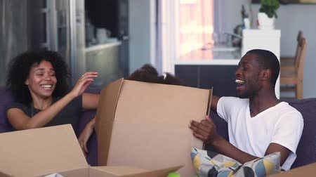 uitpakken : Happy black parents and child girl having fun on moving day, funny cute kid daughter jump out of box play in living room, excited african family laughing pack unpack boxes in new home, relocation Stockvideo