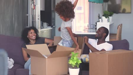 etnia africano : Happy child girl jump out of box give high five to dad play with black parents in living room, african family and kid daughter laughing having fun pack unpack enjoy relocation moving in new home