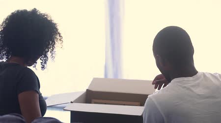 uitpakken : Rear view of happy african american couple unpacking boxes together in living room moving in new home, young black family talking laughing having fun after relocation or renovation in house or flat