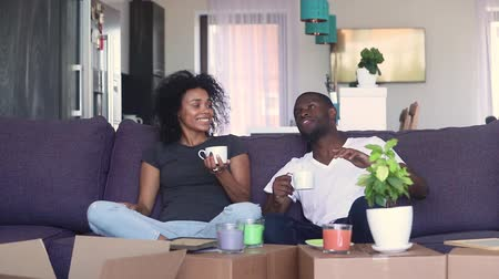 uitpakken : Happy african american couple talking drinking coffee unpacking boxes in living room moving in new home, black tenants renters settle in having fun after relocation house renovation, removals concept Stockvideo