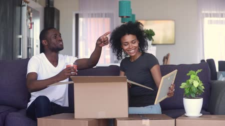 domy : Happy black couple open unpacking cardboard box parcel discussing interior design decor after relocation renovation, african family sitting on couch in living room settle in on moving day in new home