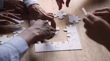 способствовать : Diverse hands of business people connect puzzle pieces together on office desk, multi ethnic team engaged in finding solution, decision making collaborate in teamwork strategy concept, close up view