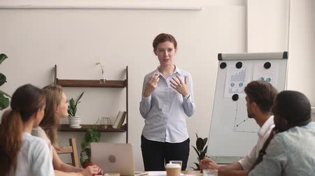 palestra : Businesswoman manager coach speaking giving flipchart business presentation at diverse sales team meeting, mentor work leader teacher consulting employees clients at group marketing office workshop Stock Footage