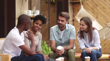 mates : African american guy talk to diverse friends tell story sit at table on cafe terrace, black mate speak to multiracial students people having fun conversation at meeting enjoy multi-ethnic friendship Stock Footage