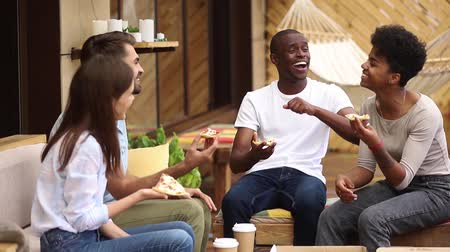mates : Multicultural happy millennial friends having fun eating sharing pizza together at meeting in pizzeria restaurant, diverse young students joking laughing sitting at cafe table in terrace outdoor