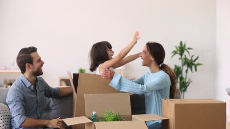 uitpakken : Happy family enjoy moving day relocation renovation, cute funny child girl jump out of box hugging mom having fun in living room, kid girl playing with parents laughing packing unpacking in new home